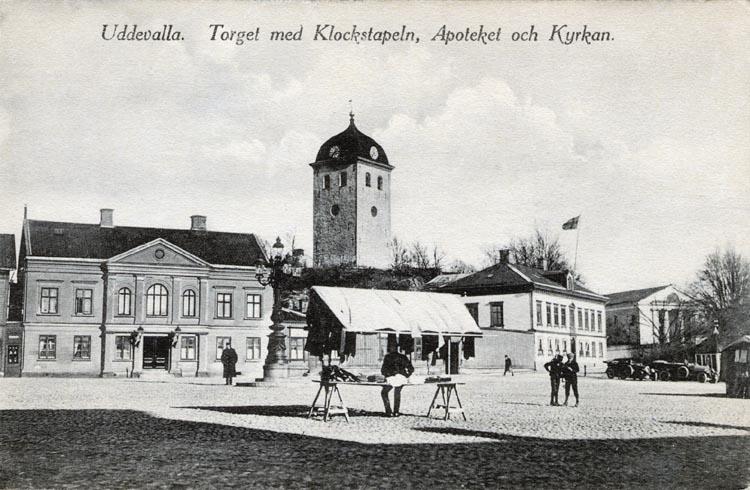 """Tryckt på kortet: """"Uddevalla. Torget med Klockstapeln, Apoteket och kyrkan."""""""