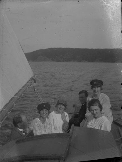 """Enl. text i blå bok: """"Personer i sittbrunnen på en segelbåt"""" ::"""