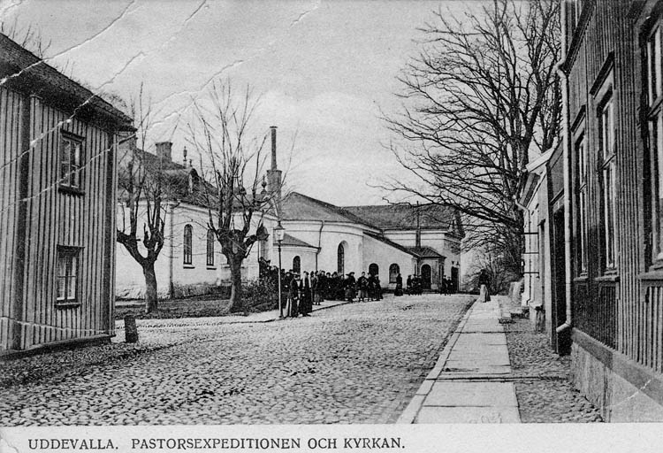 """Tryckt text på bilden: """"Uddevalla. Pastorsexpedition och kyrkan.""""    """"Förlag: Bröderna Brattberg, Uddevalla.."""""""