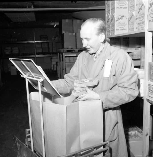 """Troligen packar butiksbiträdet ner förpackningar med dadlar. """"Eol Bolaget Julgotter 15/12 -58"""" enligt notering."""