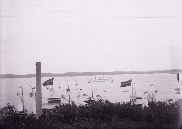 Vid H.M. Konung Oscar II ankomst till Lysekil. Kungajakten Drott efter ombyggnaden 1901. Segelbåtar. I förgrunden varmbadhuset.