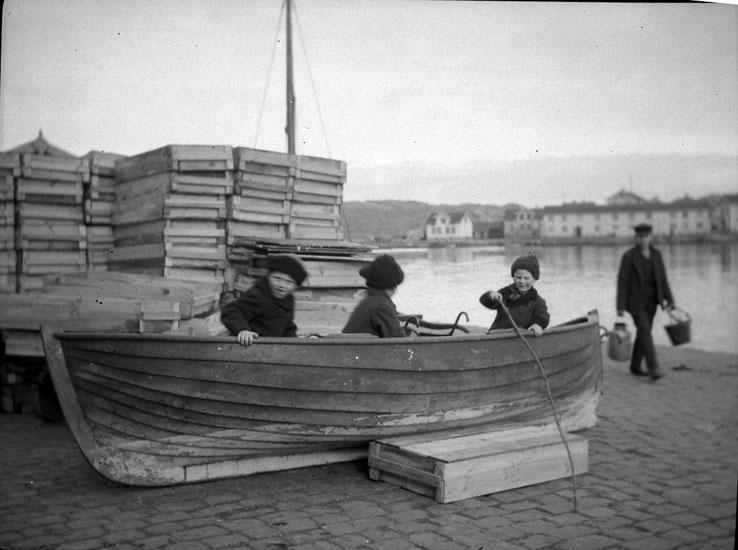 Tre barn i en båt upplagd på en kaj