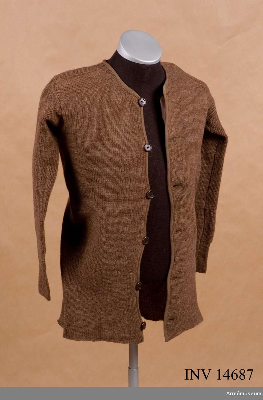 """Grupp C I Av tjockt brunt yllegarn i rockens form. Tröjan stänges på framsidan med 6 bruna benknappar. Tröjan kantad med 1 cm bred mörkbrun bård längs övre öppningen, framsidan och tröjans nedre kant. Vid övre öppningen en vit bomullsetikett med påskriften: """"F & E. TARRAT"""" firmanamnet """"Size 3"""" - storlek 3, """"1917"""".  Samhörande nr är AM.14685-7"""