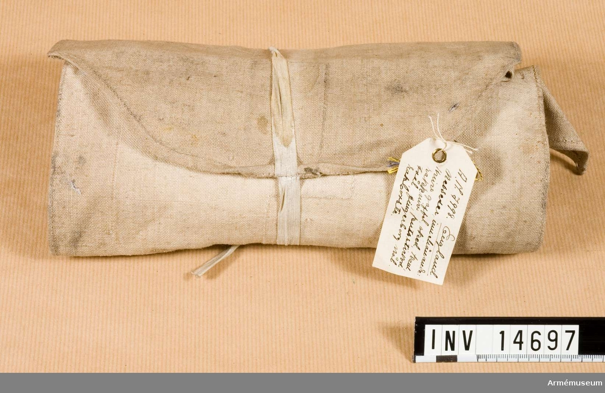 """Grupp nr C II Necessär sydd av lärft med tio fickor för olika hushålls- och rengöringstillbehör. Necessären stänges med två bomullsband och har stämpel med påskriften: """"W"""" uppåtriktad pil """"D"""". Under pilen """"28"""".  Samhörande nr är AM.14697-14707"""