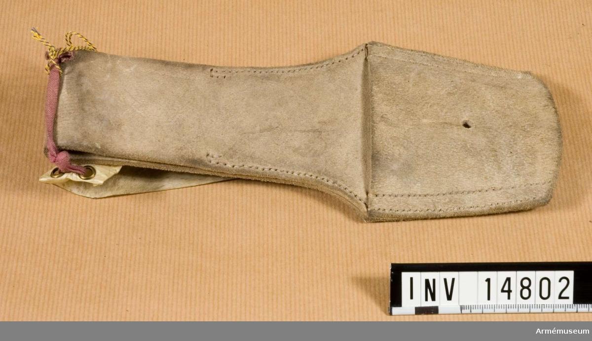 """Grupp C II Av älgläder (vitt läder) med ögla. Med denna kopplas bajonettbaljan vid hylsan, som har ett knapphål. På hylsans baksida finns stämplar: uppåtriktad pil """"W.D"""" och  """"C & M 1880"""" - för övrigt oläsligt."""