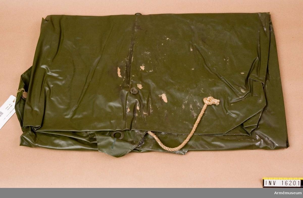 Regnskydd arbetsmodell/1967.Av olivgrön plast med hål för huvudet och med knäppanordningar för tält.