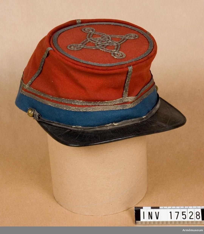 """Grupp C I. Mössa, officer/löjtnant vid 1. afrikanska hästjägarregementet. Buren av givaren  s.s löjtnant vid hästjägarreg:t åren 1863-1865. Käppi med rak svart läderskärm, med band av ljusblått kläde, b: 20 mm. Foder av gult tyg med rött läderband omkring botten. Vidare finns det en fastsydd rand pappskiva med firmaetikett där det står """"Artaub"""", """"Chapelier"""", """"Princes"""", """"Alger"""". Överskift en krona, på sidorna fanor. Hakremmar av silvergalon med två små silverknappar. Överdelen är täckt av mörkrött kläde och två silverband på nedre delen och ett på bottnen, vilka alla går runt käppin. På var sida går silverband från övre kanten till den nedre (två silverband är löjtnants gradbeteckning). LITT Handbuch der Uniformenkunde. Prof Rich. Knötel. Hamburg 1937 sid 183. Från år 1833 infördes röd fältmössa med  ljusblått band, (Under tiden blev käppin förändrad så att den liknade en tschakot) vilken användes till år 1915. Bilaga sid 5 Afrikansk Jägarofficer med samma käppi. Sid 14 kort beskrivning på offiserskäppi. Enl W Granberg."""