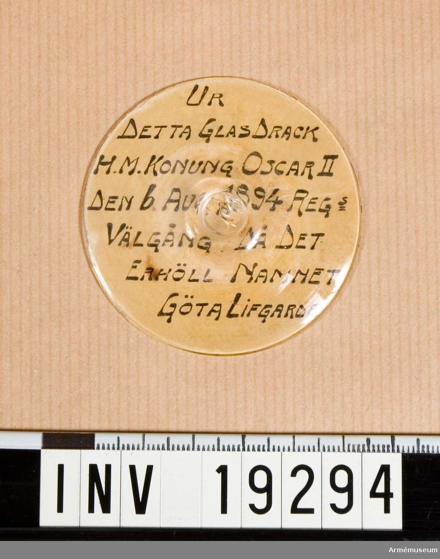 """Fot till glas (glaset bortslaget). Papper med texten: """"UR DETTA GLAS DRACK H.M. KONUNG OSCAR II DEN 6 AUG 1894 REGs VÄLGÅNG DÅ DET ERHÖLL NAMNET GÖTA LIVGARDE"""" klistrat under foten."""