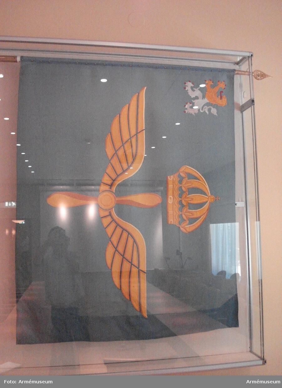 """Fanans mittmotiv har tvåd gula vingar omkring en propeller, krönt av kunglig krona. I övre högra hörnet ett västgötalejon i gult och vitt (silver) med röda klor och tunga samt 2 st stjärnor i silver. Motiven är utförda i tryckteknik. Fanstången märkt med """"Kungl. Västgöta Flygflottilj vaktfana tillverkad 1986"""".  Fanstången är delbar. 1800 och 900 mm vardera."""
