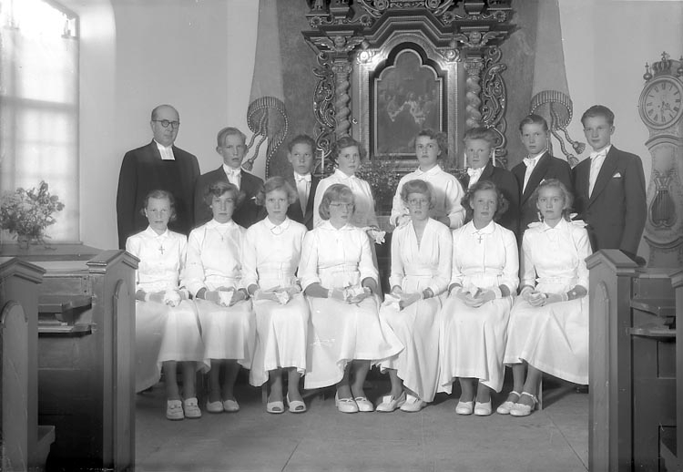"""Enligt fotografens journal nr 8 1951-1957: """"Konfirmander, Komminister Nyblom Jörlanda""""."""