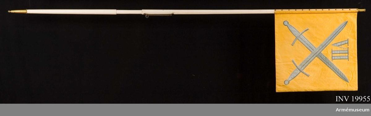 Dubbelsidig (liksidig). Bottentyg i gult siden, blå siden i applikation kantad med broderi i blått. Mellanfoder i bomullsfilt. 2 korslagda svärd med romersk 7:a (VII) mellan spetsarna. Framsidan blekt, 3 revor (9, 4, resp. 3 cm) i bortre nedre hörnet. På frånsidan en mindre reva, 2 cm,  i övre bortre hörnet. 39 st tännlikor i 3 rader. Vitmålad trästång.
