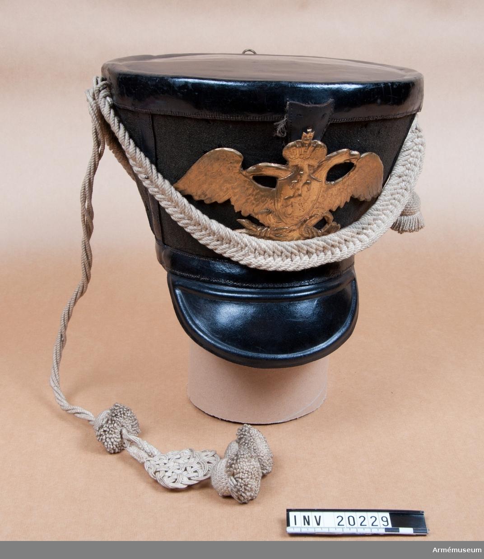 Grupp C I. Ry. kiver. Av svart kläde och svart lackerat läder. Övre delen har rund rak botten. Skillnaden mellan diametrarna på övre och nedre delen är 2,5 versch (11.1 cm). På framsidan finns en hållare för ståndare. Vapenplåt av mässing på tschakåns främre del. Plåten är graverad med en dubbelörn och S:t Göransbild. Skärm av lackerat läder. Banderoll av vita garnsnören och två tofsar. Foder av grovt brunt läder. LITT  F von Stein, Geschichte des russischen Heeres, Hannover Hannover 1885, Sida 336: Denna tschakå infördes i ryska armén den 26 september år 1817 och hade samma storlek som i boken. B Söderholm, Livgardets 2. artilleribrigads historia, S. Petersburg, 1898, sida 80  f: På gardets tschakå fanns vapen med dubbelörnen med S:t Göransbild. På sida 80 avbildas denna tschakå. Krigsenziklopedi, S. Petersburg, 1912, del VII, sida 259: Vapenplåt på denna tschakå infördes i ryska gardet år 1808.