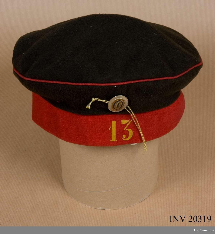"""Grupp C I. För menig vid 13. Beloserskij (""""vita sjöar"""") Generalfält- marsalk Greve Lassis infanteriregemente, 1. regemente  4. infanteridivisionen: 1882.  Mössan av kläde (tallriksmodell), består av två delar: Övre delen av svart kläde med röd passpoal på övre kanten: på framsidan en oval kokard (soldatkokard) målad i orange (S:T Görans färg). Nedre delen av rött kläde med """"13"""" på  framsidan. Siffrorna i gul emaljfärg. 13 är regementsnummer. Foder av grå linnelärft."""