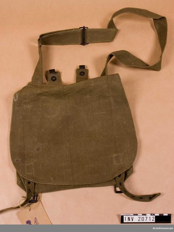 Grupp C II Mattorinst, även kallad brödväska, av grönt tyg med två järn- krokar för att hänga väskan på bälte. Två innerfickor. Axelgehäng av samma tyg mer järnspänne och ring.