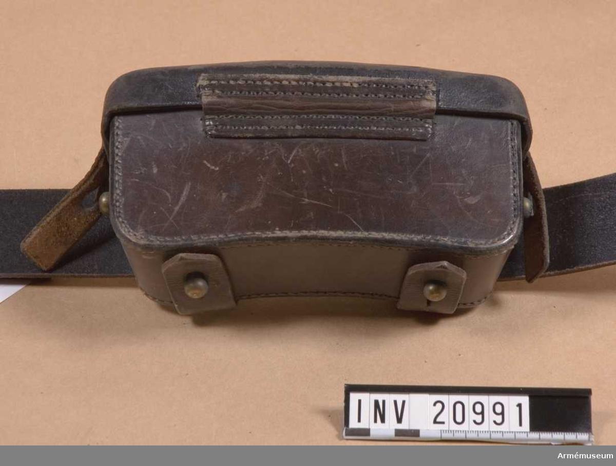 """Grupp C I. Av svart läder. Till mausergevär m/1871, kaliber 11 mm, för 30 patroner i varje.  LOCK som stängs med läderbitar och knapphål på sidorna. På lockets baksida finns en tryckt stämpel med text """"Loch- Söhne Berlin.""""  VÄSKA med på sidorna två mässingsknappar för stängning. På baksidan två hylsor av samma läder för att fästa den vid livrem och en mässingsring för att koppla tornistremmar."""