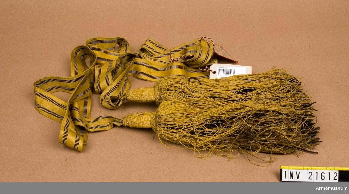 """Grupp C I. Av band och två tofsar. Band av gult silke, b: 35 mm, virkat med två svarta ränder på sidorna. Tofsar; övre delen är av trä och betäckta med gult tyg och brodering i gult silke på ena sidan med dubbel örn och den andra namnchiffer """"F.I. I"""" =Kejsar Franz Josef I. Nedre delen består av snören, l:250 mm - de inre av svarta, tjocka snören och de yttre av gula, tunna. En kartongetikett med text """"Officersskärp tillhörigt en vid Magonta den 4 juni 1859 stupad österikisk officer därstädes funnet samt skänkt till Artillerimuseum av Generalmajoren John Lilliehöök. Skärpet och tofsar har några fläckar, troligen av blod.Generalmajor Lilliehöök tjänstgjorde år 1859 vid Zouaverna och deltog i franska fälttåget i Italien och Algeriet. LITT  Adjustirungs-Ausrüstungs (Vorschrift) für das K.K. Heer, I Theil, Wein 1871. Sida 111, 112,. Feldbinde. Bestämmelser och mått för officerarnas paradskärp vilkas längd är dubbelt krop- pens omfång."""