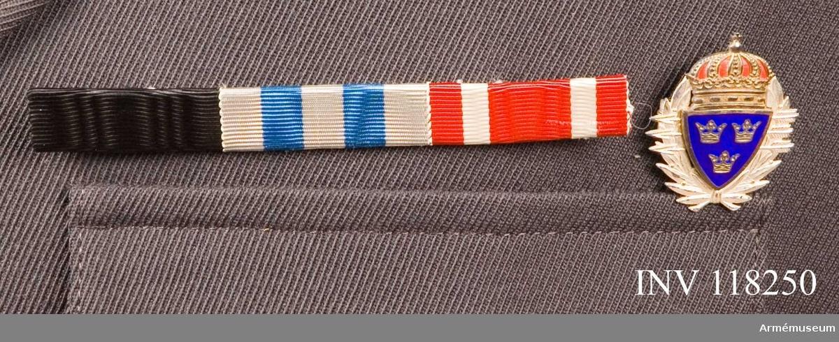 Grupp C I.  På vapenrock m/1960. Ur uniform för regementsläkare vid Kungliga Norra Smålands regemente Består av rock, långbyxa, skjortor, slips, paradskärp, kappa, mössor, halsduk.