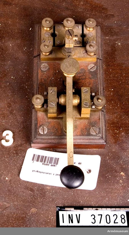 """Grupp H I.  Monterad på träplint tillsammans med kopplingssegment och """"polskruvar"""". Nyckeln företer stor likhet med Telefon A/B L M Ericssons nutida (19300-40-tal? reg.anm) telegrafnycklar för brandstationer och som dessa nycklar icke har blivit nämnvärt ändrade är det troligt att Lars Magnus Eriksson själv har utfört denna nyckel emedan han åren 1866-1872 arbetade hos Öller & Co."""