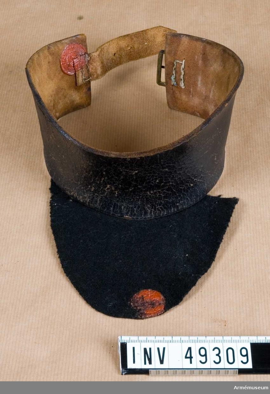 Grupp C I. Av svart läder med mässingsspänne och klädesflik.