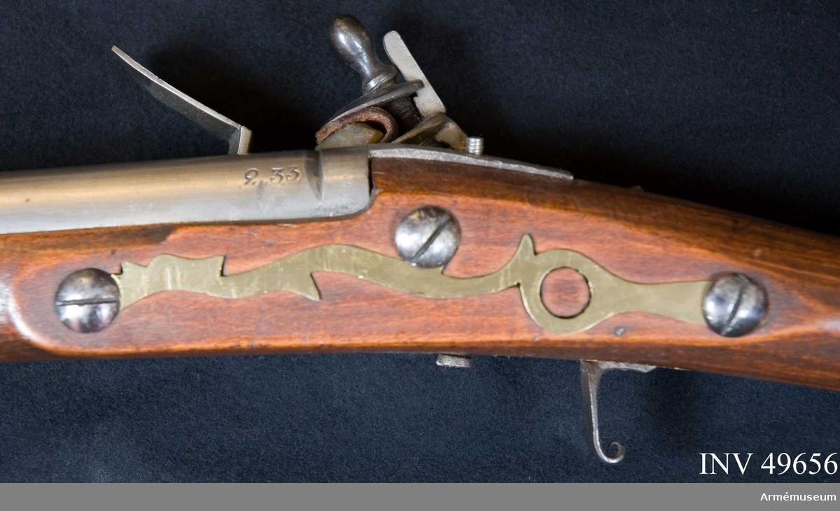 """Grupp E XIV. Loppets relativa längd är 68,1 kal. Afrikanskt gevär med flintlås. Bakplåt, varbygel, rörkor och  laddstock fattas. Låsblecket är platt och signerat """"BARKER"""". På  pipan och kolven återfinns nummer """"233""""."""