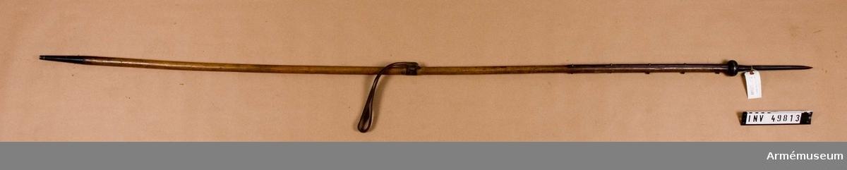 """Grupp D I.  Spjutbladet är tveeggat med höga ryggar.  Holken är konisk och har på sin nedre del en vulstliknande stötskivan. Den sistnämda består av två halvor, som hålls samman och fast av en skruv,  vilken går genom de bägge halvorna och genom holken.    Skaftskenorna är kullriga med avrundade ändar. Spets och skenor är svartfernissade. På den ena skaftskenan sitter 3 järnöglor, vid vilka flaggan skulle fastgöras. På holken står 129 och nedtill på den ena skenan är """"129 2 U R I"""" inslaget. De nitar, som håller fast skenorna, har höga, kullriga huvud.  Skaftet är av ask och brunt med en största diameter av 27,5 cm. Doppskon är av järn samt 15,8 cm lång och konisk med tvärt avskuren nedre ände. Armremmen är av brunt läder och är fastsurrad vid skaftet med en  smal, brun läderrem. Ett på skaftet inslaget stift betecknar  armremmens rätta plats.  Mått: Spjutbladets längd 20,5 cm Spjutbladets bredd nedtill 2,65 cm Stötskivans höjd 3,25 cm Stötskivans diameter 5,55 cm Skaftskenornas längd 54 cm Skaftskenornas bredd 1,25 cm"""