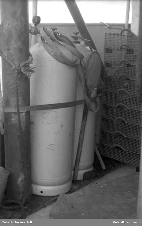 """Enligt fotografens noteringar: """"Gastuberna som används till räkkokning. Det är gasol, varje tub rymmer 50 kg och det räcker högst två veckor. Man har seriekopplat de båda tuberna för att få ut det mesta ur dem.""""  Fototid: 1996-03-06."""