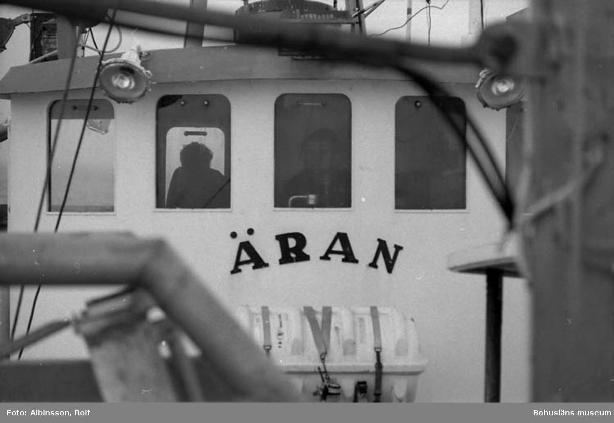 """Enligt fotografens noteringar: """"Akterut mot hytten. Bengt Persson styr, Harald Hansson kikar på trålen akterut."""" Fototid: 1996-03-06."""