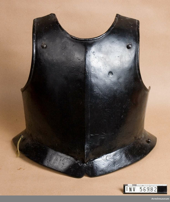 Grupp D IV. Kyrass till halvrustning, Sverige. 1600-1650-tal. Målad i svart. Visst remtyg utbytt. Fästen till remspännen på axlar utbytta. Eventuellt sammansatt av från början ej samhörande delar. Alla tre remmarna som invändigt håller upp höger arm är brustna och ersatta med glödgad ståltråd. Samma gäller för vänster arm. De båda remmar som över båda axlarna skulle ha hållit samman kyrassens fram- och bakstycke saknas nästan helt. Av remmen som skulle ha hållit upp höger arm återstår endast en kort bit. Färgbortfall av äldre datum på kyrassens bakstycke.