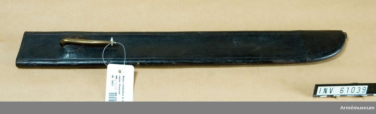 """Grupp D II.                             Baljan är av svart, tjockt läder. Nedtill finns en doppsko av  mässing, som dock med undantag av spetsen betäcks av lädret. Upptill finns en koppelhake, som sitter på en rund skiva, vilken är fastsydd vid lädret. På koppelhaken förekommer siffran 16. I Modellsalens reversal tillsammans med de franska  faskinknivarna AM 60480-1, 56496-7, 56500-1 upptagen som  """"Huggare med baljor, utländska, franska, 4 st."""" I  Artillerimuseum fördes detta vapen tillsammans med 61066-7  (österrikiskt) åren 1879-84 som """"2 st huggare med sågklingor och  baljor för pionjärer; Österrike 1831"""". Ännu i 1911 års  inventarium kallas AM 61028-9 """"Huggare, (faskinkniv) med  sågklinga och balja för pionjärer, Österrike"""". I 1912 års  inventarium sammanfördes vapnet med AM 56814-5 som """"2 st  faskinknivar med sågklinga och baljor, äldre modell för  pionjärerna; 1810-1855, Preussen"""". Vapnet tillhör sannolikt det  parti preussiska vapen, som 1828 hitsändes på föranstaltande av  dåvarande kronprins Oscar."""