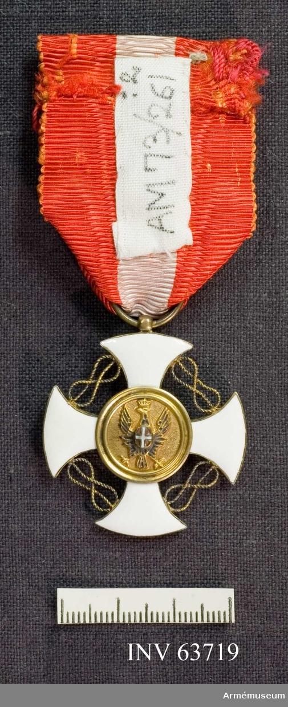 """Grupp M II. Ett mantenanskt (?) kors där korsarmarna har rundade ändar. Korset är av vit emalj och guldkantat. Mellan korsarmarna åtta formade figurer av tvinnade, gyllene trådar. Mittglob som på åtsidan är guldkantad. Blå emalj med en gyllene krona i mitten. Frånsidans glob har i relief krönt örn med utbredd avingar i guld och en röd sköld med vitt kors på bröstet. Medaljband, b: 38 mm, kluvet rött-vitt-rött och med röd-vit""""krouton""""."""