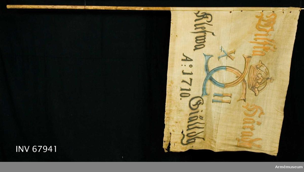 """Duk: Tillverkad av enkel vit linnelärft, sydd av två horisontella våder. Duken fastspikad vid stången med järnspikar på ett linneband.   Dekor: Målad endast från dukens insida, i mitten Karl XII:s namnchiffer dubbelt C med XII på ömse sidor, krönt med sluten krona, i gult och brunt i det övre fältet och blått och svart i det nedre. Text på ömse sidor om chiffret; upptill i gult, nedtill i svart.  Stång av furu.   Lapp på stången: """"Tillhör Klefwa kyrka, inskuret K (Cederström)."""