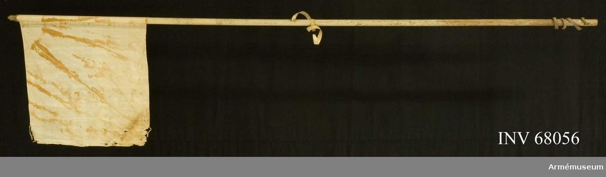 Duk: Enkel, tillverkad av vit sidentaft. Duken fäst vid stången med en rad tennlickor på mönstervävt band.   Dekor: Saknas.  Stång: Vitmålar, smal. Två skinnremmarremmar är instuckna i stången, den övre är vit.  Har holk.