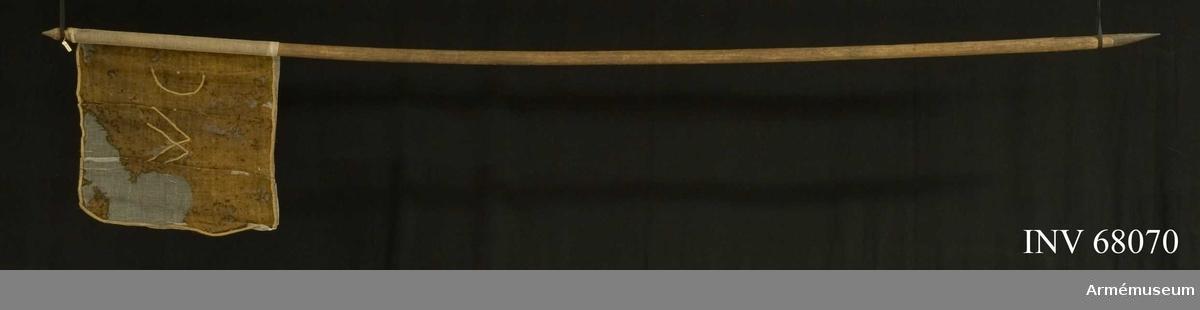 Duk: Enkel, tillverkad av roströd yllekypert. Fäst vid stången med förtenta spikar på ett vitt band.  Dekor: I mitten påsydda vita band (snoddar) i form av text. Kantad med vitt linneband.  Stång: Tillverkad av brunsvart ask. Liten spets svarvad i toppen på stången. Spetsliknande kläde av järn med fäste en bit upp på stången.