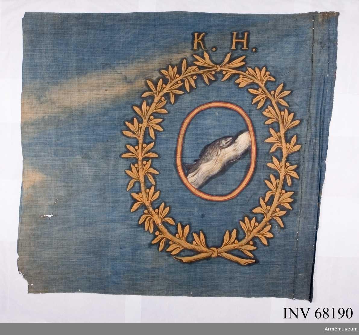 Duk: Tillverkad av enkel blå linnelärft. Två våder sammansydda. Fåll åt fandukens utsida. Vertikala ytterkantsfållen lagd åt utsidan. Duken fäst med häftstift på felsida.  Dekor:  Målad, omvänt lika på båda sidor. En oval sköld med gul och liten röd kant vari en böljande vatten, och i strömmen en uppåt simmande fisk.  Skölden omslutes av en upptill och nedtill hopknuten krans av två lagerkvistar i gult med bär också i gult. Bokstäver i gult längs överkanten.  Stång: Tillverkad av trä, grönmålad. Avsågad.