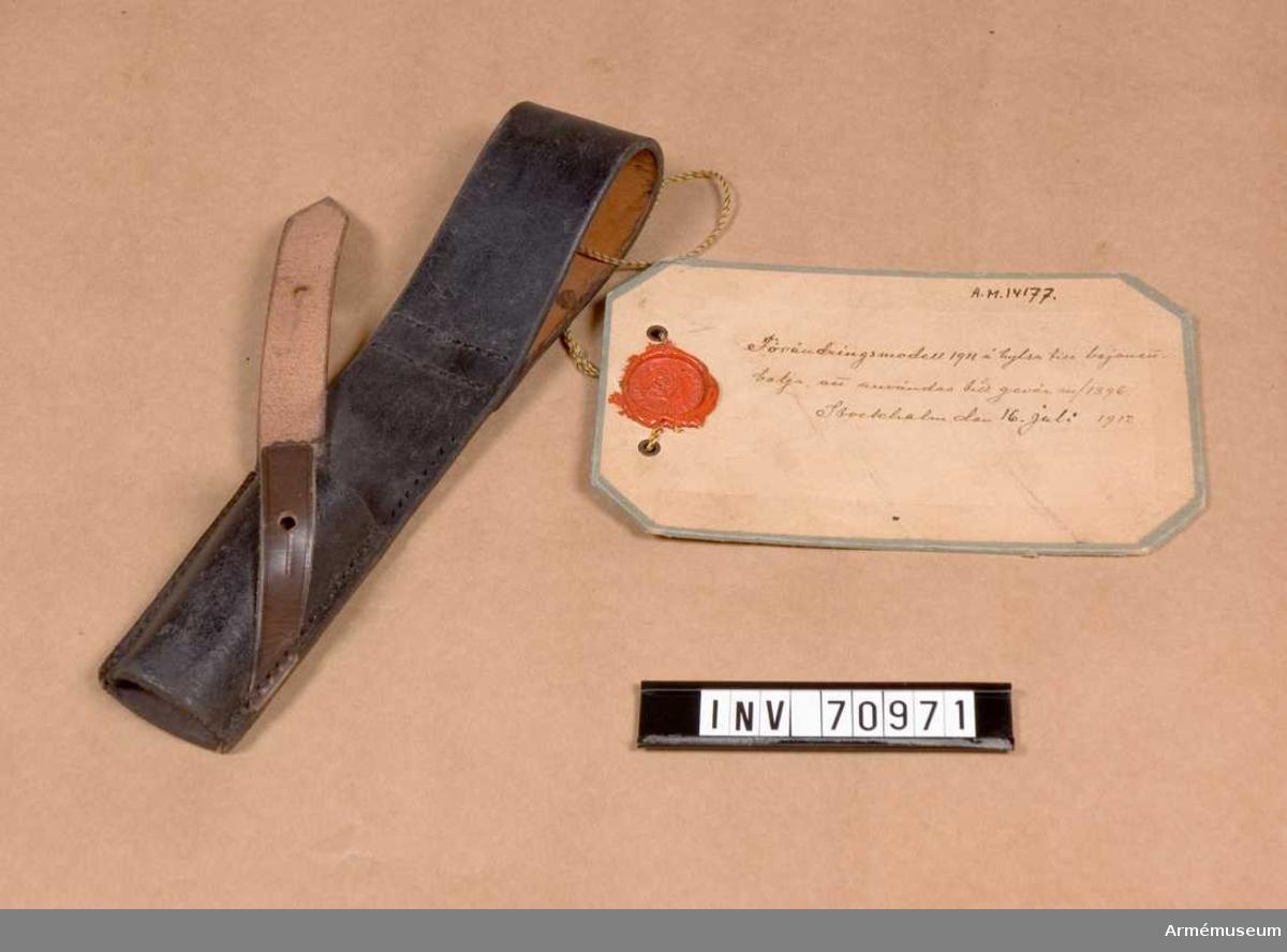 """Grupp C:II.  Vidhängande modellapp: """"Förändringsmodell 1911 å hylsa till bajonettbalja, att användas till gevär m/1896. Stockholm den 16. Juli 1912.""""."""