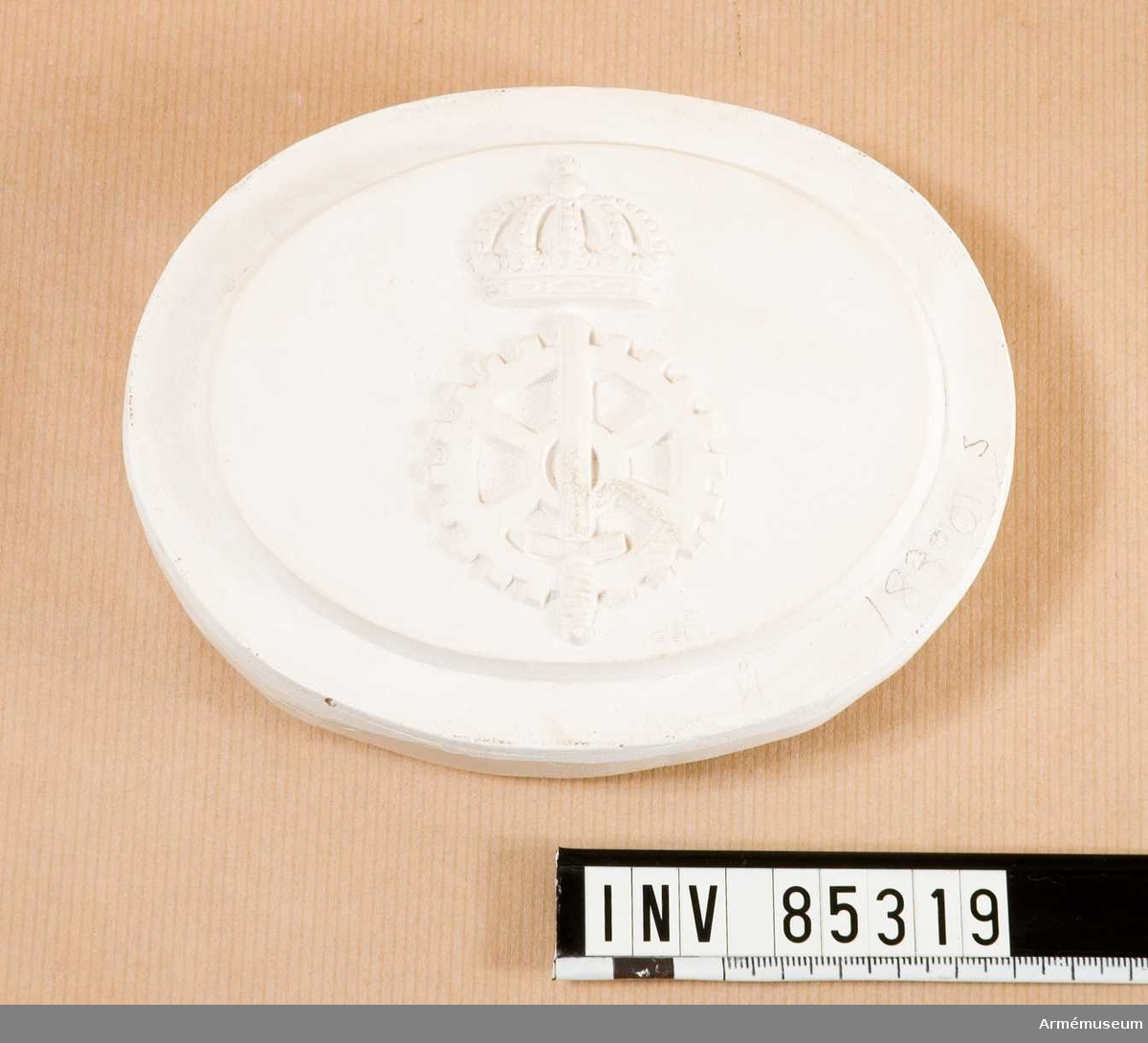 Grupp M V. Modell i gips till stansar för emblem, 16. No 1833 Försvarets fabriksstyrelse.