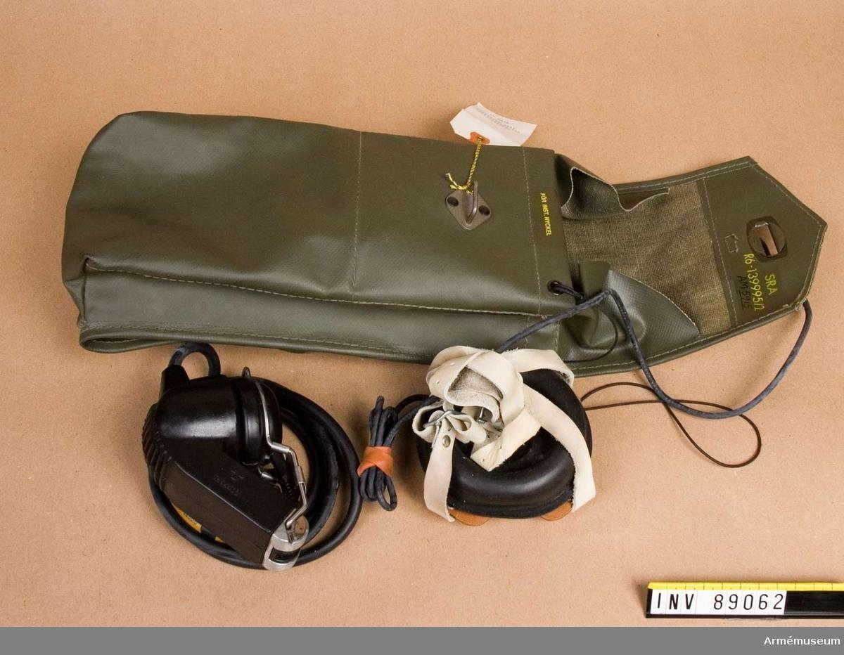 Packficka av grön galonväv. I packfickan: antennsladd, förlängningssladd, hörlur, isärtagbar telefonlur.