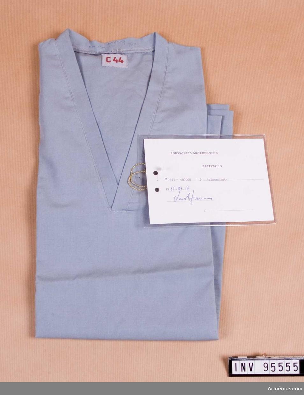 """Vidhängande etikett: """"Försvarets materielverk Fastställs M 7325-007000-3, Pyjamasjacka, 1985-09-18 (oläslig underskrift)""""."""