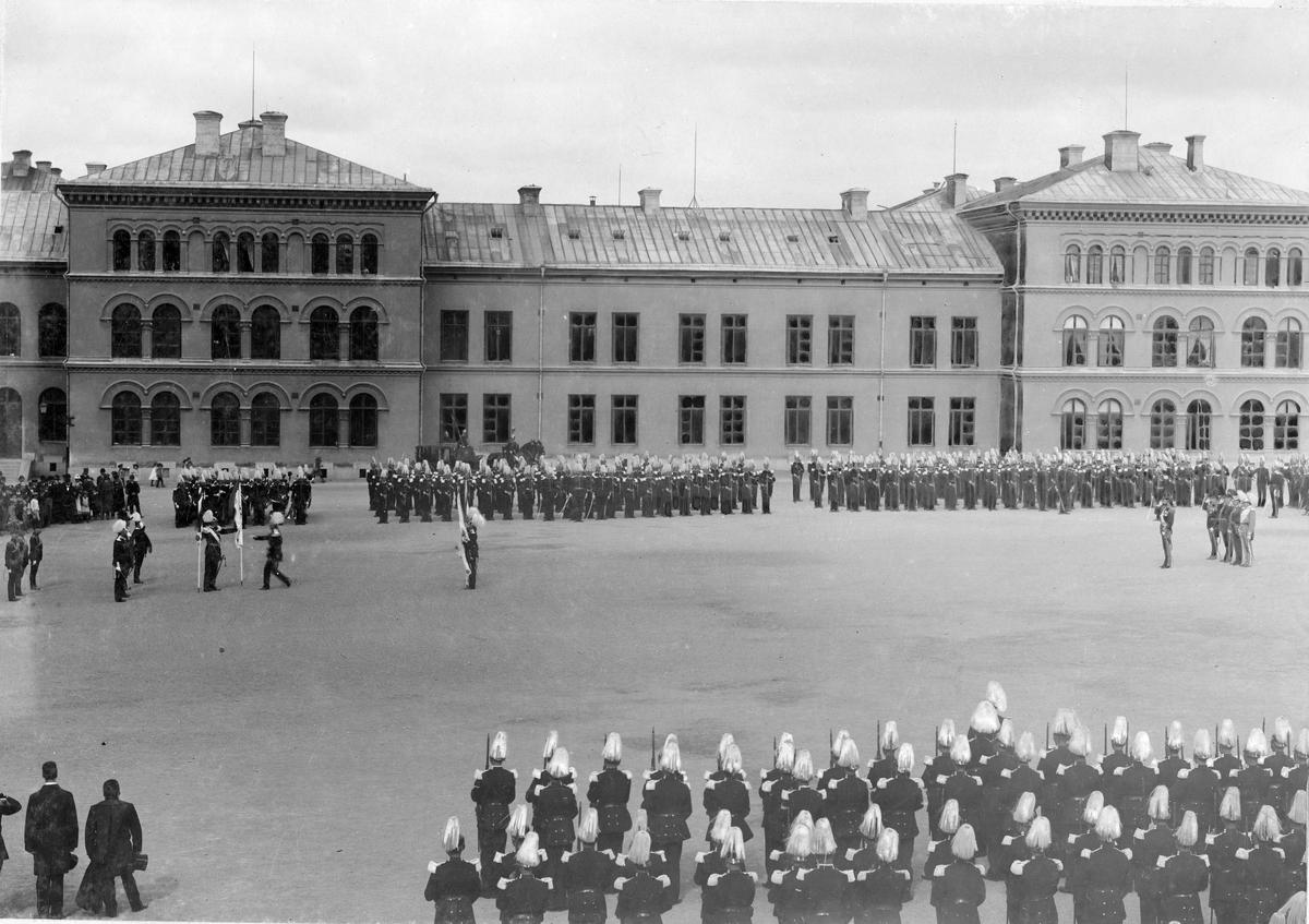 Kung Oscar II delar ut fanor åt Göta livgarde I 2 utanför regementet på Storgatan i Stockholm. Civila åskådare ser på i bakgrunden.
