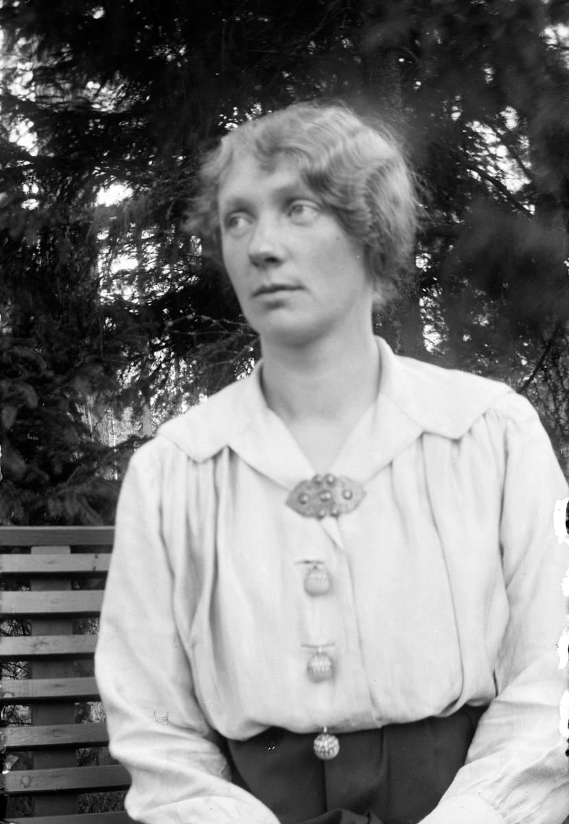 En kvinna sitter på en bänk med skog och vatten i bakgrunden.