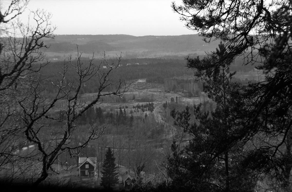 Uppifrån en höjd har man utsikt över skog och åkrar. Ett hus med uthus ligger nedanför sluttningen.