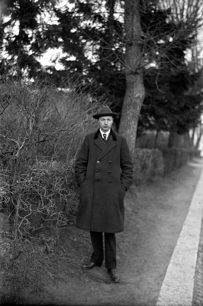 Gustav Andersson klädd i rock och hatt, står vid en vägkant. Bredvid honom växer en avlövad buske och i bakgrunden syns träd och en häck.