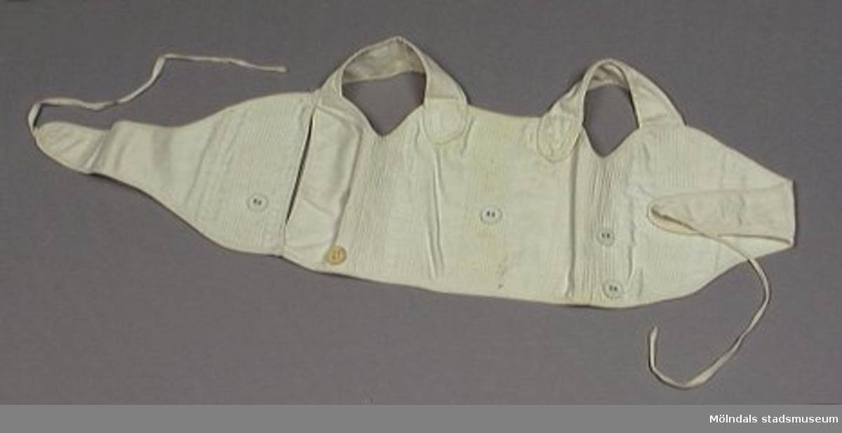 Litet livstycke för barn i vit bomull. Knyts omlott. Fem klädda knappar, två i var sida, en mitt fram.