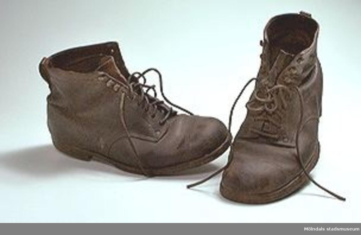 Bruna läderkängor för man. Snörning med läderband genom hål och hankar. Lädersula.Klack av gummi med järnskoning. Skänkta till givaren av en släkting 1966. Givaren har låtit halvsula dem och använde dem vid bergsbestigning av Kebnekaise och berg i Afrika.