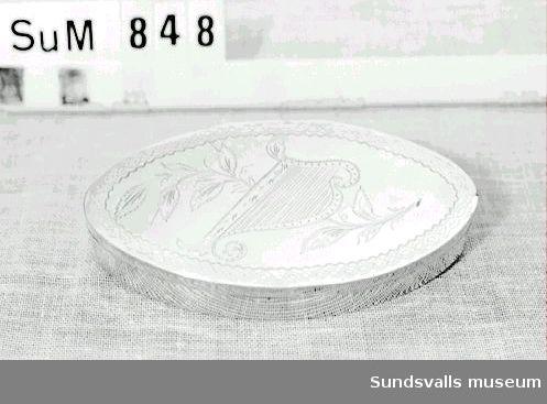 Snusdosa i silver. Spetsoval. På locket svisselerade brodyrer, samt svisselerad och graverad kvist och harpa. På lockets insida är 'SCMD' inristat. Stplr: Nils Johan Hagman, Sundsvall 1843.