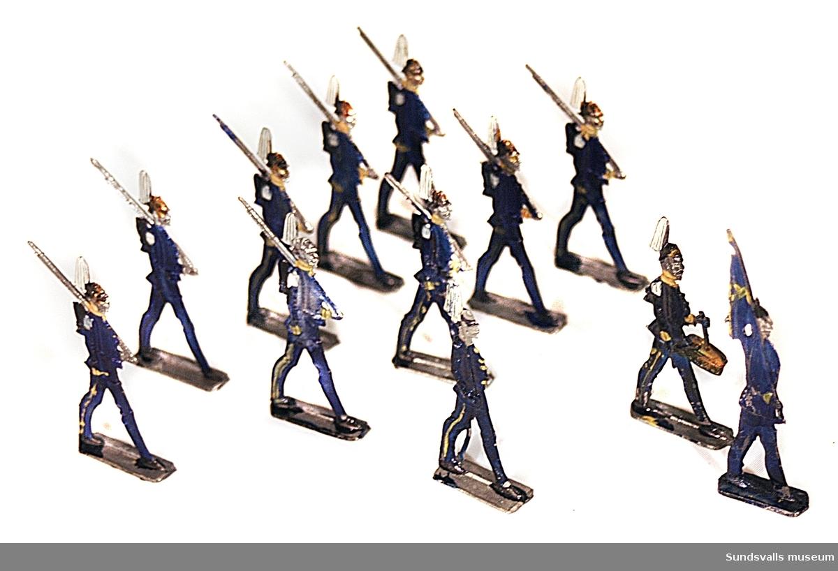 SuM 2757:1-12 tennsoldater. Platt form. En stycken fanbärare, en stycken sabelbärare, en stycken trumslagare och nio stycken med gevär i marschställning. Originalförpackning märkt 'Preuss Infanterie Sturm, G H, Made in Germany'.