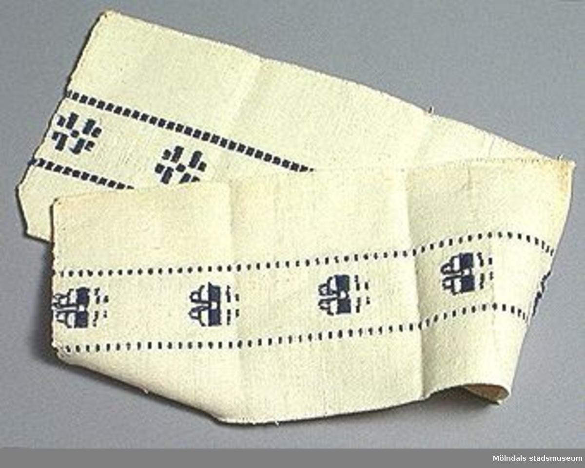 Naturvit botten med blått inslag i mönsterbård.Elevarbete från textillärarseminariet.Gåvan förmedlad genom Gustav Wickström.