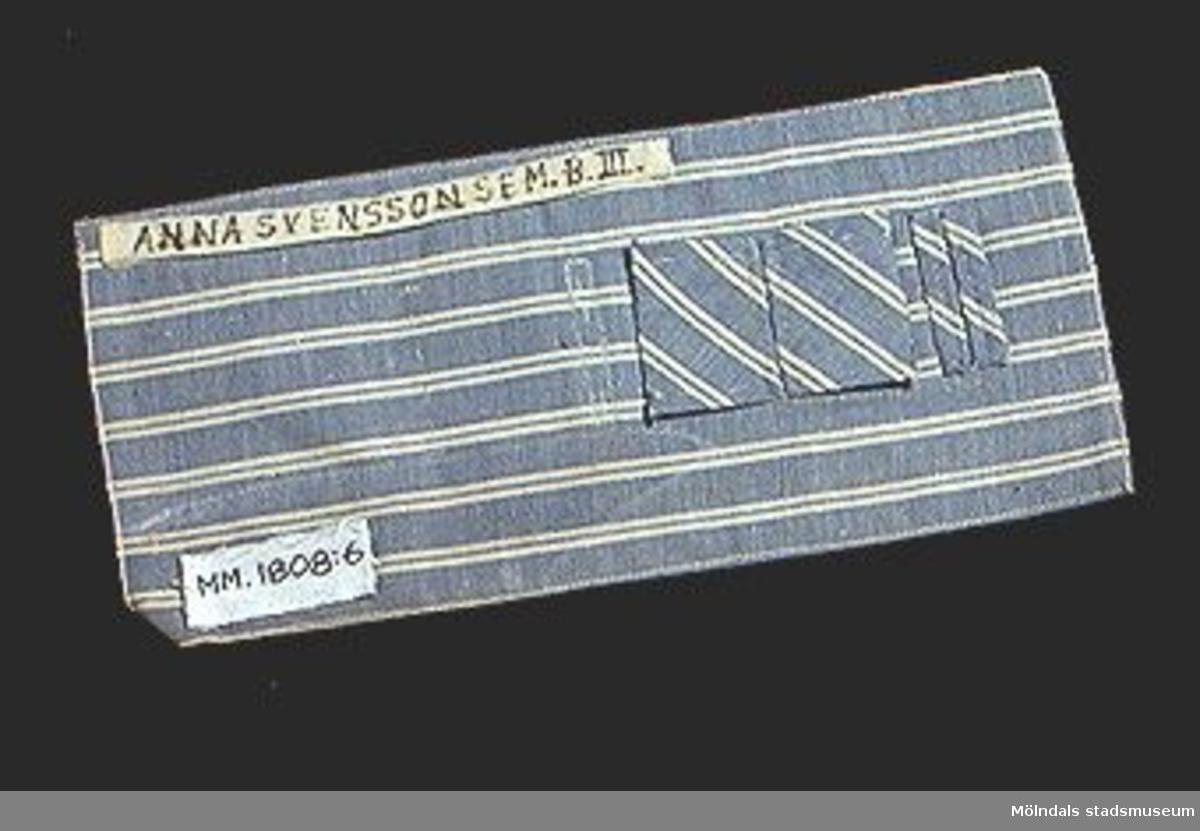 Prov på knapphål med kantskoning. Blått och vitrandigt tyg.Elevarbete från textillärarseminariet.Gåvan förmedlad genom Gustav Wickström.