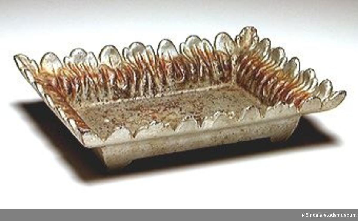 """Grå och tung rektangulär spottkopp med de uppvikta sidorna utformade som eldflammor eller blad/växt-dekor. Bottens undersida märkt: Göteborgs mekaniska verkstad. Karl-Magnus Andersson (kallad """"Matrosen"""") var morfar till givaren.Han var mästare vid Götafors. Omkom i Vargön 1894. (Donatorn vet och kan berätta mycket mer).Spottkoppen stod på golvet så man vid behov kunde spotta ut saliv, snus eller tuggtobak. I botten la man granbarr för att det skulle lukta gott. Spottkoppar användes fram till 1930-talet."""