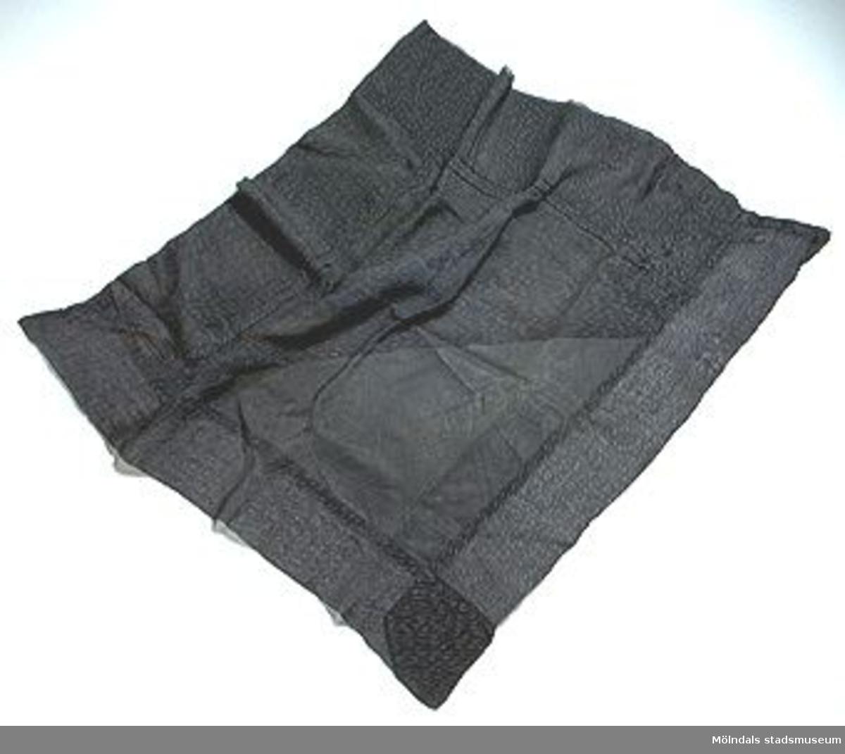 Svart, kvadratisk schal av tunt sidenfodrat plisserat tyg.Har troligen tillhört Clara Hasselberg (1863 - 1942). Därefter använd av dottern Karin Hasselberg (1903 - 1996).